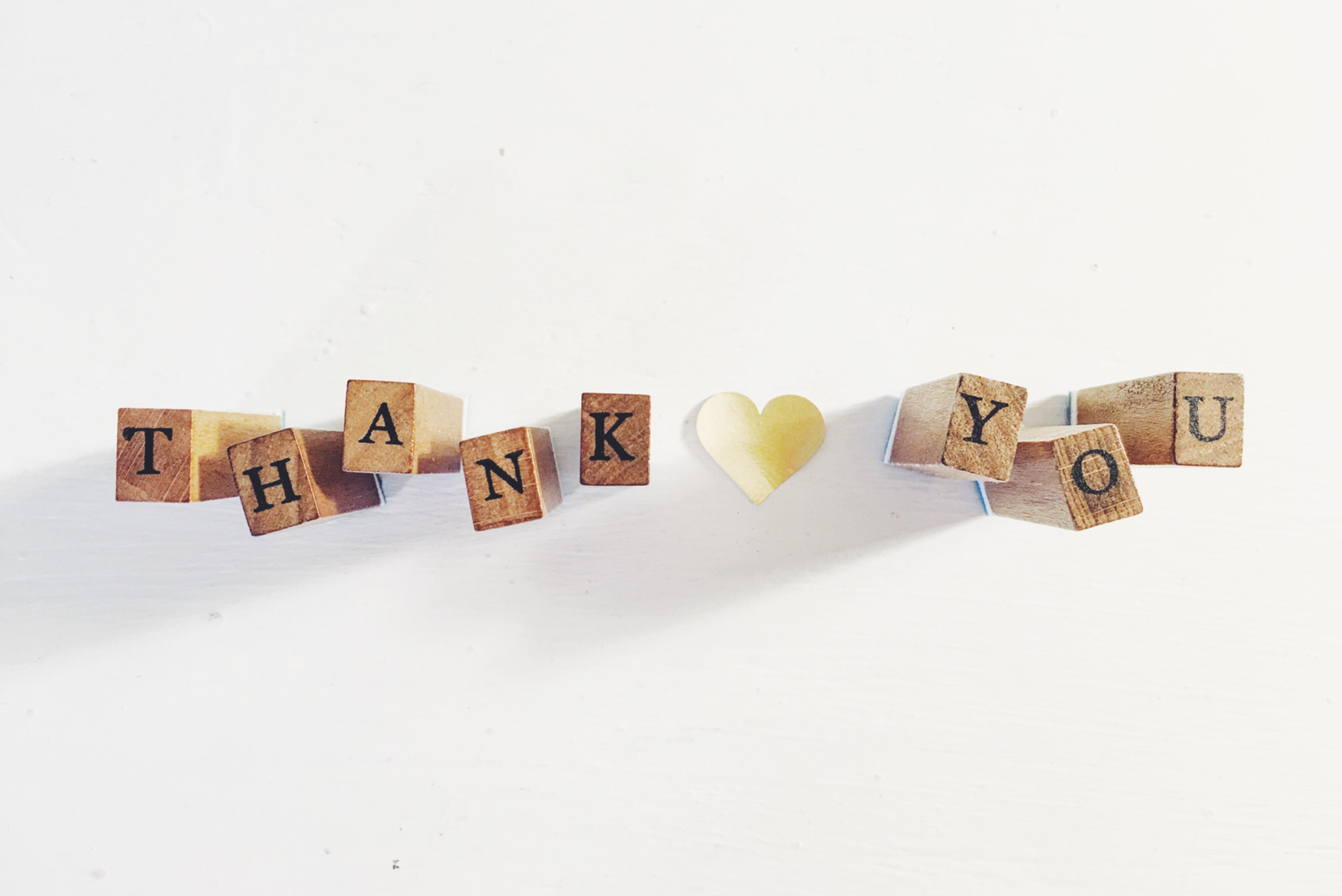 "wooden stamps spell out ""thank you"" against white background"