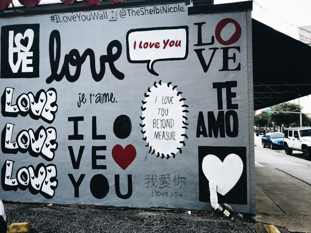 A wall with grafitti that says I Love You in several languages.