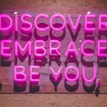 """pink neon sign says, """"discover, embrace, be you."""""""